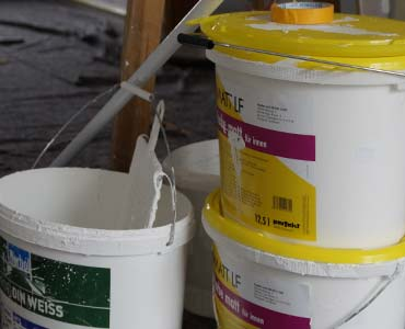 Opened paint buckets and paintbrushes