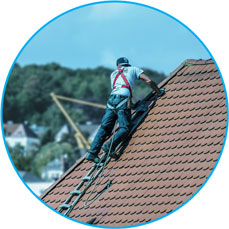 Roof tiler worker at the top of the house